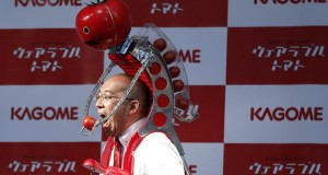 Kagome Co's employee Shigenori Suzuki tries to eat a tomato which is fed to him by the newly-developed `Wearable Tomato` device for runners, during its unveiling event ahead of the weekend's Tokyo Marathon in Tokyo